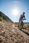 People in the mountains on a bike races to victory — Stock Photo