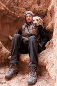 A man walks in mountain with labrador dog — Foto Stock