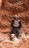 A man walks in mountain with labrador dog — Стоковое фото