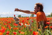 People play with the dog on the wild tulips — Stock Photo