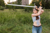 Fragile girl with a huge sword — Stock Photo