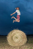 Man jumping on a hay field — Foto Stock