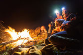 Bonfire in a camp in the mountains and the light of flashlights — Stock Photo