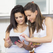 Two smiley girls with tablet pc — Stock Photo