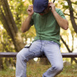 Boy relaxing and listening to the music in the park — Stock Photo
