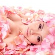 Asian girl in rose petals — Stock Photo