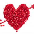 Pomegranate seeds in heart shape with arrow. — Stock Photo