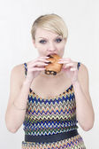 Young beautiful woman with big appetite eats a soft, fresh roll — Stock Photo