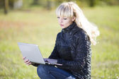 Beautiful young girl outdoors with laptop — Stock Photo