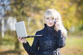 Beautiful young girl outdoors with laptop — Zdjęcie stockowe