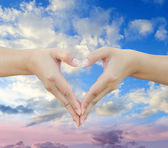 Hands shaping a heart on sky — Stock Photo