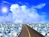 Asphalt road ,ice cubes in blue sky — Stock Photo