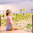Beautiful girls sit on  pond in summer  — ストック写真