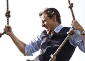 Strong, able businessman climbing ropes — Stock Photo