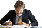 Angry businessman at desk — Stock Photo