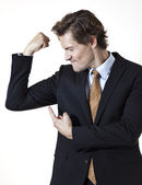 Businessman showing off mucsles — Stock Photo