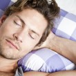 Young man lying in bed — Stock Photo