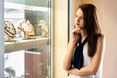 Beautiful girl choosing jewelry in shop — Stock Photo