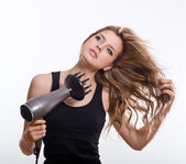 Brunette woman blow-drying long hair — Stock Photo