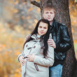 Loving pregnant couple walking in the autumn park — Stock Photo