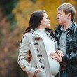 Pregnant woman and her husband walking in the autumn Park — Stock Photo