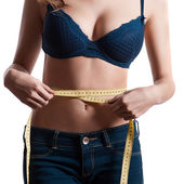 Woman measure her waist by metre-stick — Stock Photo
