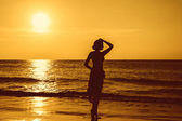 Silhouette young woman on the beach at sunset. — Stock Photo