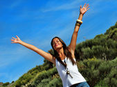 Happy woman standing with outstretched arms — Stok fotoğraf