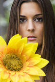 Portrait of woman with yellow flower — Stock Photo
