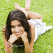 Stock Photo: Young womlying on grass