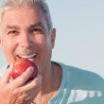 Senior male biting an apple — Stock Photo