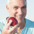 Senior man holding an apple — Stock Photo #28486177