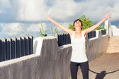 Woman with open arms enjoying the sun — Stockfoto