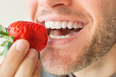 Man eating strawberry — Stock Photo