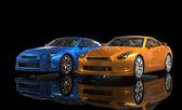 Blue and orange metallic cars on black background — Stockfoto
