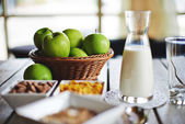 Green apple on wooden table over bokeh — Stock Photo
