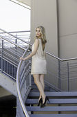 Sexy blonde woman in cocktail dress ascending staircase — Stock Photo
