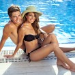 Happy beautiful young couple at the swimming pool — Stock Photo #28245677