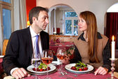 Man and woman staring at each over a meal — Stock Photo
