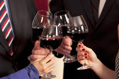Clinking glasses with red wine. — Stock Photo