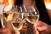 Clicking glasses with white wine. — Stock Photo