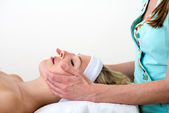 Masseuse performing a facial massage on a woman. — Stock Photo