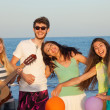Group of young people enjoying beach party with playing guitar a — Stock Photo