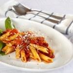 Pasta on white plate with tomato sauce — Stock Photo