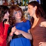 Three women in a bar talking. — Stock Photo