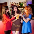 Three women in a bar holding glasses. — Stock Photo