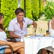 Friends enjoying a meal in a tropical garden — Foto de Stock