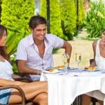 vrienden genieten van een maaltijd in een tropische tuin — Stockfoto