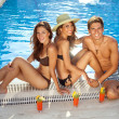 Friends sunbathing at edge of pool — Stock Photo #29785387