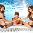 Three friends toasting each other at the pool — Stockfoto